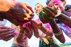 Young multiethnic friends holding colorful paint in hands at holi festival. Close-up partial view of young multiethnic friends holding colorful paint in hands at Stock Image