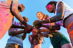 Young multiethnic friends holding colorful paint in hands at holi festival. Low angle view of young multiethnic friends holding colorful paint in hands at holi Royalty Free Stock Photography