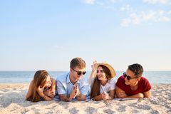 Young multiethnic group of people relaxing on the beach towel near the sea on white sand. Stylish friends hanging on the stock image