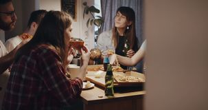 Young multiethnic happy male and female friends having pizza and drinks, talking at house kitchen party slow motion. stock footage