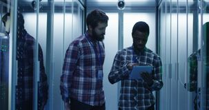 Diverse IT specialists with tablet in server room. Young multiethnic men using tablet and diagnosing server hardware while walking in data center corridor