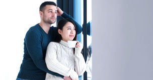 Multiethnic couple relaxing at modern home indoors Stock Photos