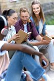 Multiethnic students studying together. Young multiethnic students studying and reading books while sitting outside university building Royalty Free Stock Photo