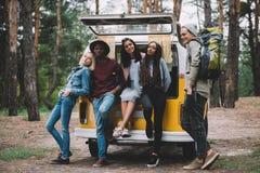 Multiethnic travelers near minivan in forest. Young multiethnic travelers posing together near retro minivan in forest Stock Image