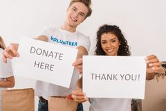 Volunteers holding charity placards. Young multiethnic volunteers holding charity placards Royalty Free Stock Image