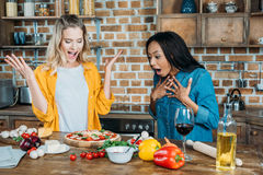 Young multiethnic women cooking pizza at home Stock Photo