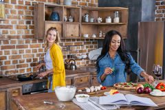 Young multiethnic women cooking together in kitchen Royalty Free Stock Images