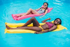 Young multiethnic women floating on inflatable mattresses in swimming pool. At resort stock image