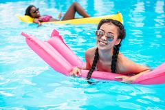 Young multiethnic women floating on inflatable mattresses in swimming pool. At resort stock photography