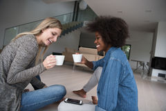 Young multiethnic women sit on the floor and drinking coffee Stock Photos