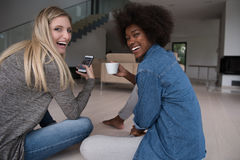 Young multiethnic women sit on the floor and drinking coffee Royalty Free Stock Image