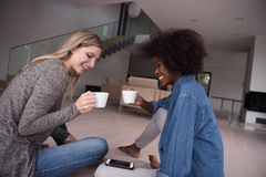 Young multiethnic women sit on the floor and drinking coffee Stock Photo