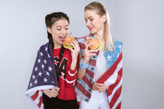 Young multiethnic women with USA flag eating American burgers Royalty Free Stock Photo