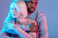 Young multiracial couple embracing over blue background. Young multiracial couple embracing over isolated blue background, men protecting his girlfriend from bad stock image
