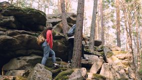 Young multiracial couple is hiking climbing up mountains, African American man is helping woman giving her hand and. Young friends multiracial couple is hiking stock video