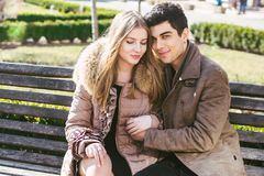 Young multiracial couple, male and female heterosexual students in love. A date in a city park on a wooden bench. Young brunette. Men with dark skin and a royalty free stock photography