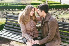 Young multiracial couple, male and female heterosexual students in love. A date in a city park on a wooden bench. Young brunette. Men with dark skin and a stock image