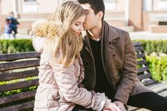 Young multiracial couple, male and female heterosexual students in love. A date in a city park on a wooden bench. Young brunette. Men with dark skin and a royalty free stock image