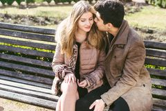 Young multiracial couple, male and female heterosexual students in love. A date in a city park on a wooden bench. Young brunette. Men with dark skin and a stock photos