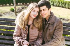 Young multiracial couple, male and female heterosexual students in love. A date in a city park on a wooden bench. Young brunette. Men with dark skin and a royalty free stock photo