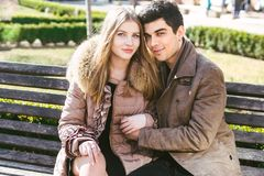 Young multiracial couple, male and female heterosexual students in love. A date in a city park on a wooden bench. Young brunette. Men with dark skin and a royalty free stock photos