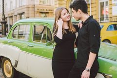 Young multiracial couple, male and female lovers heterosexual people students. Beautiful models posing standing near a retro car. In the city. Dressed in black stock photo