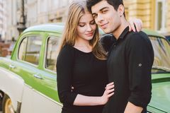 Young multiracial couple, male and female lovers heterosexual people students. Beautiful models posing standing near a retro car. In the city. Dressed in black royalty free stock images
