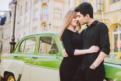 Young multiracial couple, male and female lovers heterosexual people students. Beautiful models posing standing near a retro car. In the city. Dressed in black stock photos