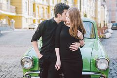 Young multiracial couple, male and female lovers heterosexual people students. Beautiful models posing standing near a retro car. In the city. Dressed in black royalty free stock photo