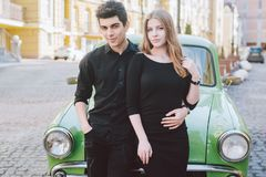 Young multiracial couple, male and female lovers heterosexual people students. Beautiful models posing standing near a retro car. In the city. Dressed in black royalty free stock image