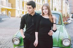 Young multiracial couple, male and female lovers heterosexual people students. Beautiful models posing standing near a retro car. In the city. Dressed in black stock photography