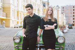 Young multiracial couple, male and female lovers heterosexual people students. Beautiful models posing standing near a retro car. In the city. Dressed in black royalty free stock photos