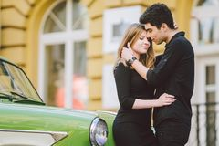 Young multiracial couple, male and female lovers heterosexual people students. Beautiful models posing standing near a retro car. In the city. Dressed in black stock image
