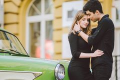 Young multiracial couple, male and female lovers heterosexual people students. Beautiful models posing standing near a retro car. In the city. Dressed in black royalty free stock photography