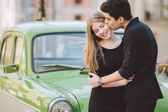 Young multiracial couple, male and female lovers heterosexual people students. Beautiful models posing standing near a retro car. In the city. Dressed in black stock images