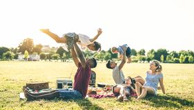 Young multiracial families having fun playing with kids at pic nic barbecue party - Multicultural joy and love concept. With mixed race people together with royalty free stock image