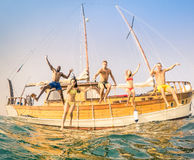 Young multiracial friends jumping from wooden sailboat Stock Images