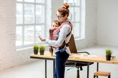 Businesswoman with her baby son at the office stock images