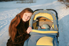 Young mum with a carriage Royalty Free Stock Image