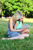 Young mum with children. Young mum reads to the children the book during walk in park Stock Image