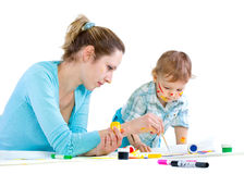 Young mum draws with the son paints Royalty Free Stock Images
