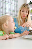 Young mum feeds the daughter in cafe Royalty Free Stock Photography