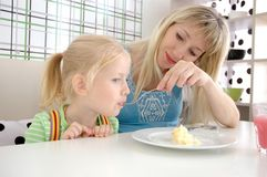 Young mum feeds the daughter in cafe Royalty Free Stock Images