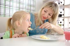 Young mum feeds the daughter with a potato Royalty Free Stock Image