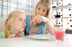 Young mum feeds the daughter with a potato Royalty Free Stock Images