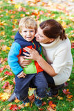 Young mum and her little kid son hugging together in autumn park. On sunny day in colorful clothes Royalty Free Stock Photography