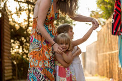 Young mum holding her blonde daughter girls on her arms smiling. Warm sunset light. Family summer travel vacations at Stock Photo