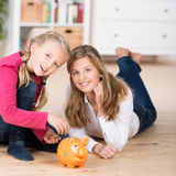 Young Mum teaching her daughter to save Stock Photo
