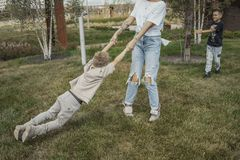 Young mum turning around, whirling with her sons at park. Happy family concept royalty free stock photo