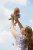 Young mum walks with the child. Young women with the small child against the blue sky Royalty Free Stock Images